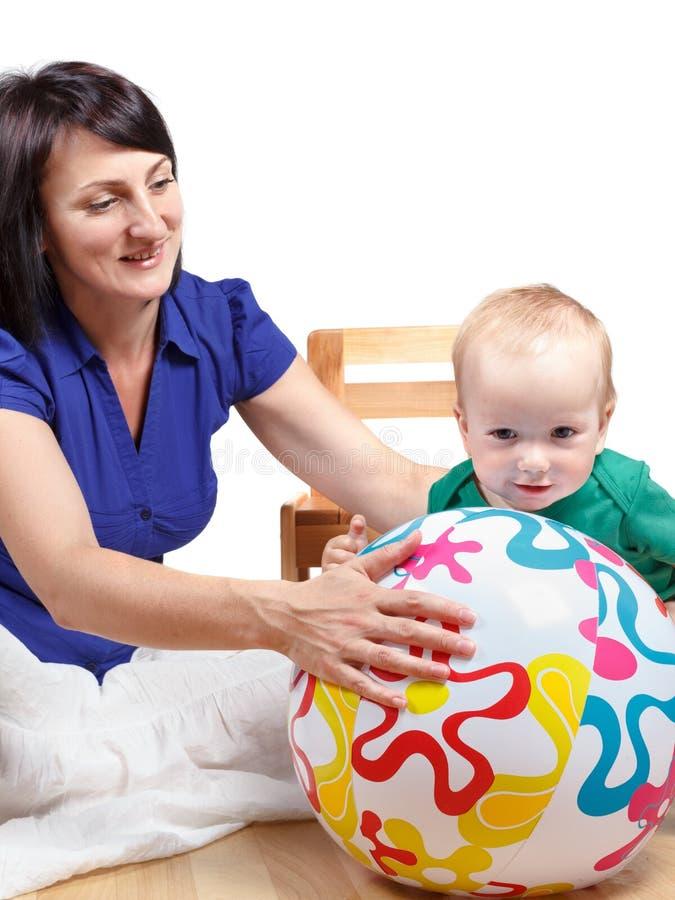 Игры мамы с ее шариком непоседы младенца Изолировано на белизне стоковые фотографии rf