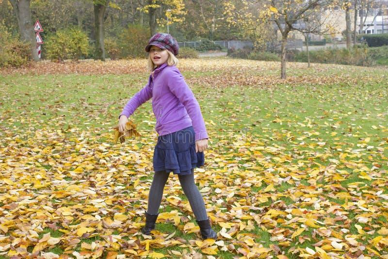 Игры маленькой девочки с листьями осени стоковые изображения rf