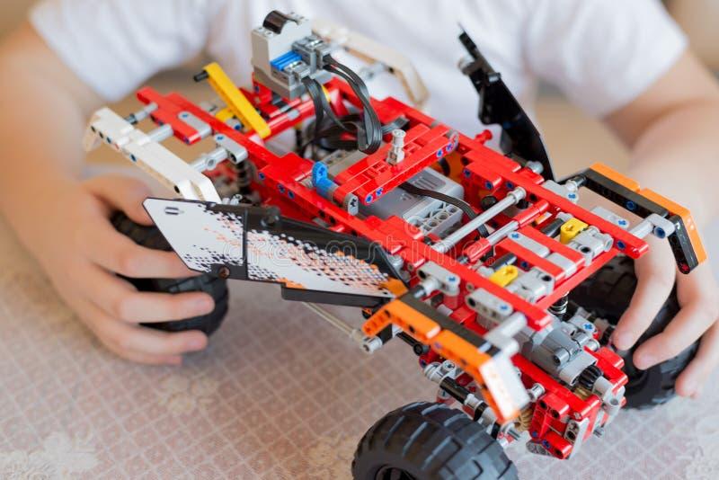 Игры мальчика собирают от конструктора автомобиля стоковое фото