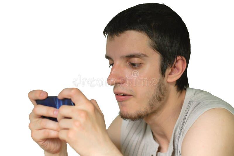 Игры молодого человека на smartphone стоковое изображение