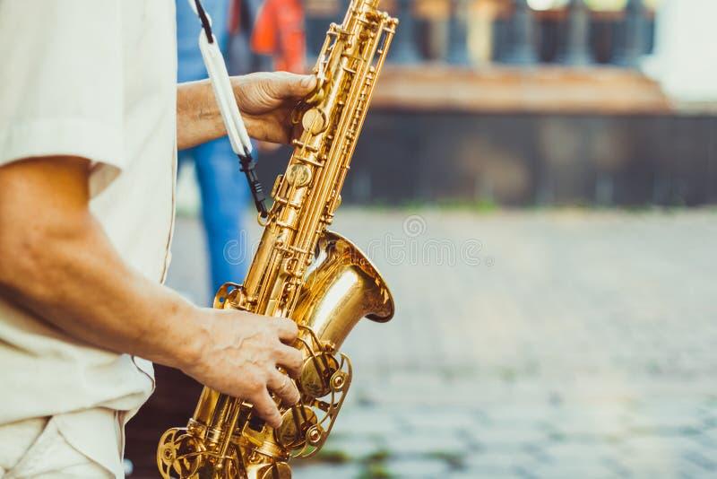 Игры саксофониста на улице стоковые фото