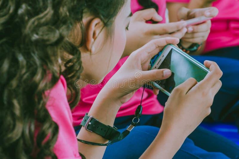 Игры игры студентов с мобильными телефонами стоковая фотография rf