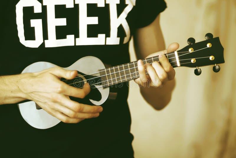 Игры человека на гитаре гавайской гитары стоковое фото