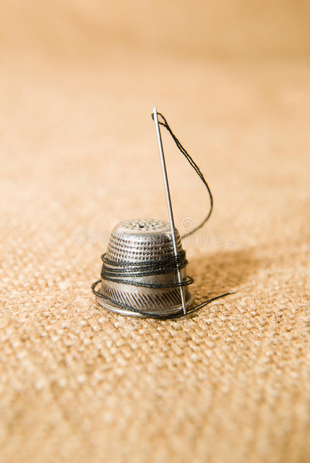 Игла и кольцо на старой ткани стоковое фото