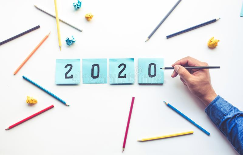 Идеи 2020 дела с номером текста сочинительства человека на notepaper стоковые изображения rf