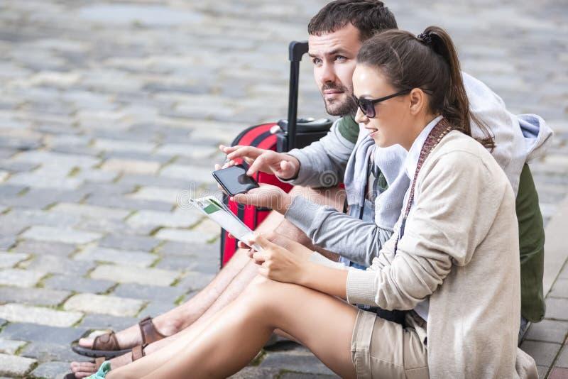 Идеи перемещения Молодые кавказские пары путешествуя вокруг города Сидеть на поле и искать назначение со смартфоном и картой стоковые фото