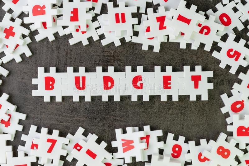 Идея бюджета, зигзаг головоломки обилия белый с алфавитами совмещает слово БЮДЖЕТ и другую черноту surrround частей письма и темн бесплатная иллюстрация