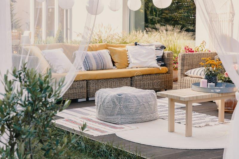Идея дизайна террасы с набором мебели сада ротанга и уютными подушками и половиком, реальным фото стоковая фотография rf