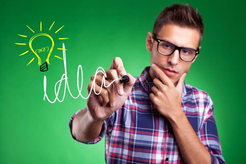 Идея и электрическая лампочка вскользь человека wrtiting стоковая фотография