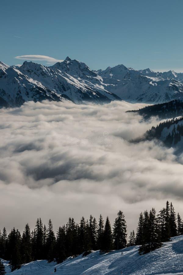 Идите снег на верхней части гор и тумана вниз с долины стоковое изображение