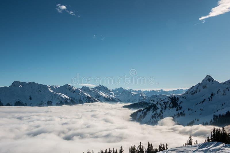 Идите снег на верхней части гор и тумана вниз с долины стоковые изображения rf