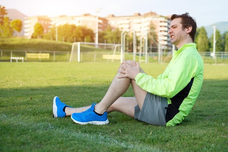 Идущая боль чувства спортсмена из-за раненой ноги стоковые изображения