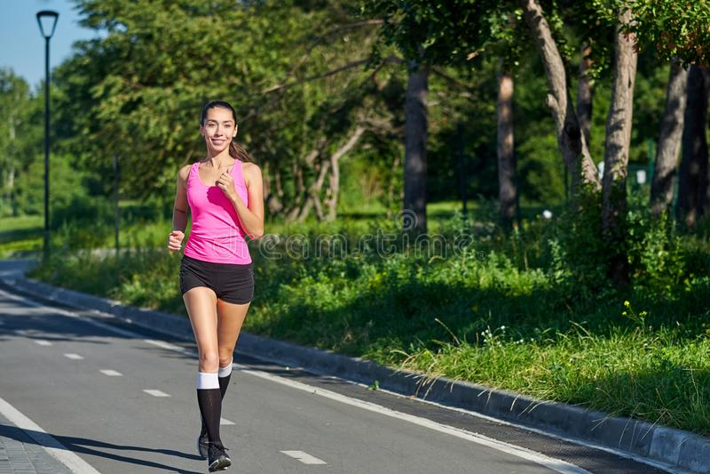 Идущая женщина на беговой дорожке во время встречи Женский бегун практикуя на трассе атлетики стоковая фотография