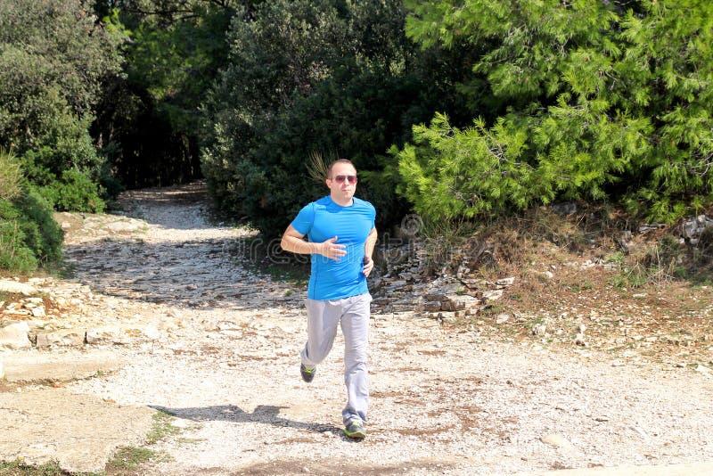 Идущая мышечная тренировка бегуна спортсмена человека внешняя в спортсменах бегуна леса идущих нося sportswear в по пересеченной  стоковое фото