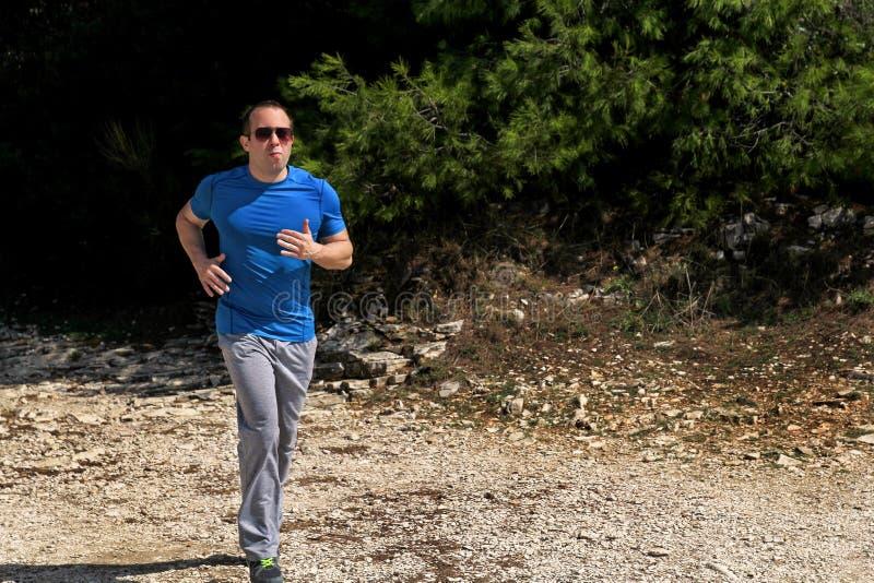 Идущая мышечная тренировка бегуна спортсмена человека внешняя в спортсменах бегуна леса идущих нося sportswear в по пересеченной  стоковые фотографии rf