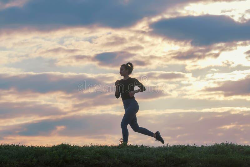 Идущая разминка утра женщины Женский бегун Jogging во время восхода солнца Разминка в парке Sporty молодая женщина Модель фитнеса стоковые фотографии rf