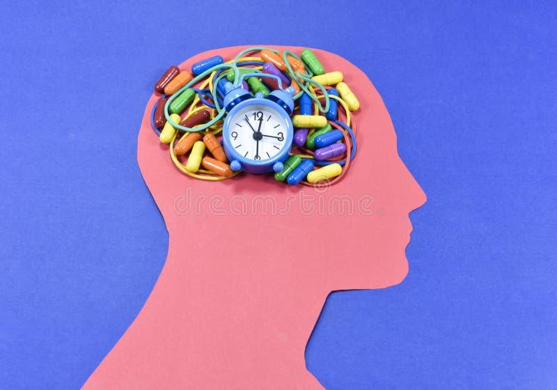 Идущие часы, покрашенные пилюльки и круглые резинкы на головном контуре стоковое изображение rf