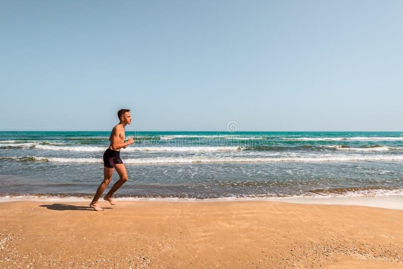 Идущий спортсмен на пляже стоковая фотография rf