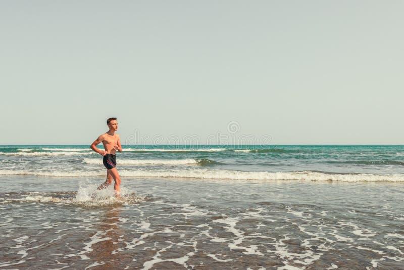 Идущий человек на пляже стоковые фотографии rf