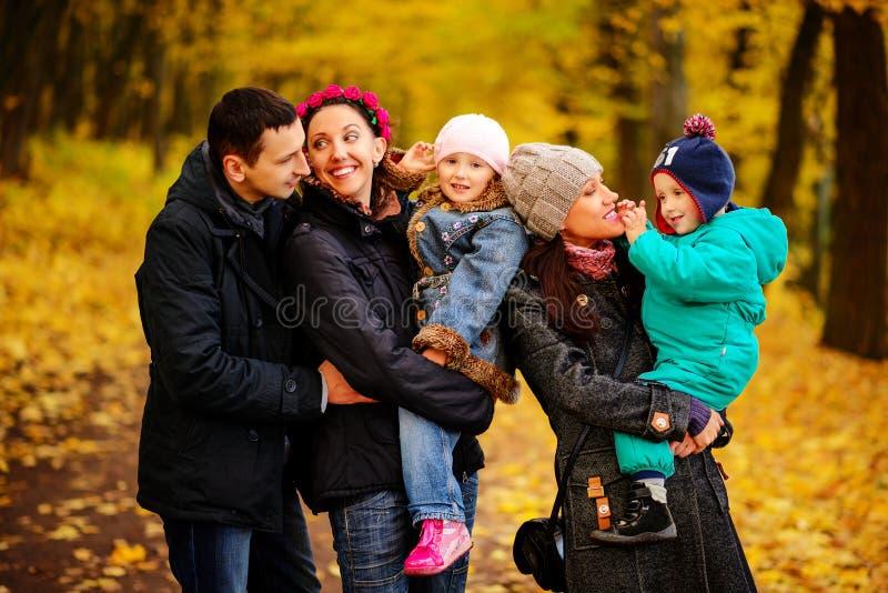 Идя семья с 2 детьми в осеннем парке стоковое фото