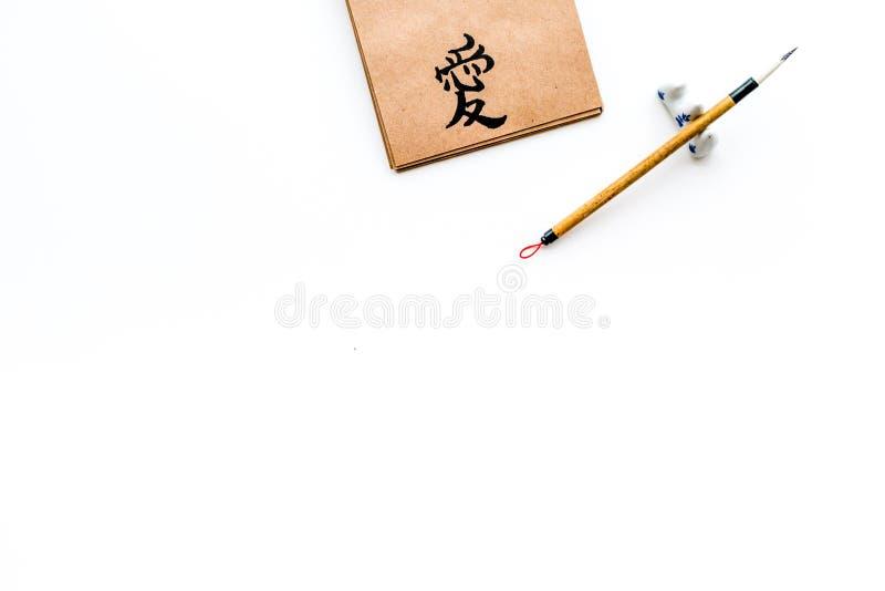 Иероглиф который значит любовь на английском Урок концепции каллиграфии Бумага около записи аксессуаров на белизне стоковые фотографии rf