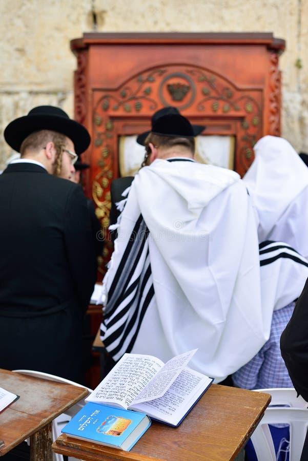 ИЕРУСАЛИМ, ИЗРАИЛЬ - АПРЕЛЬ 2017: Talmud Tora Tanach записывает лежать на таблице во время молитвы в церемонии Mitzwa бара на зап стоковые фотографии rf