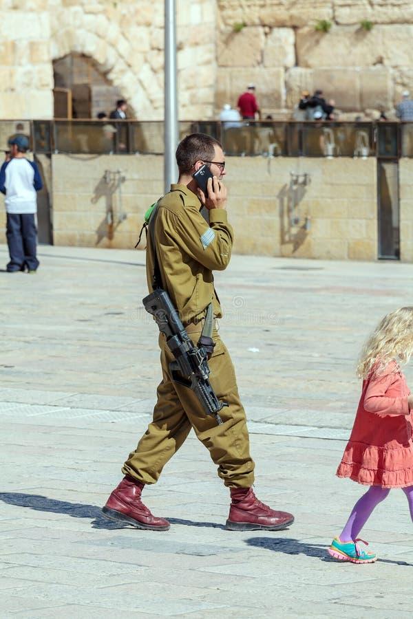 ИЕРУСАЛИМ, ИЗРАИЛЬ - 17-ОЕ ФЕВРАЛЯ 2013: Вооруженный молодой солдат говорит стоковая фотография