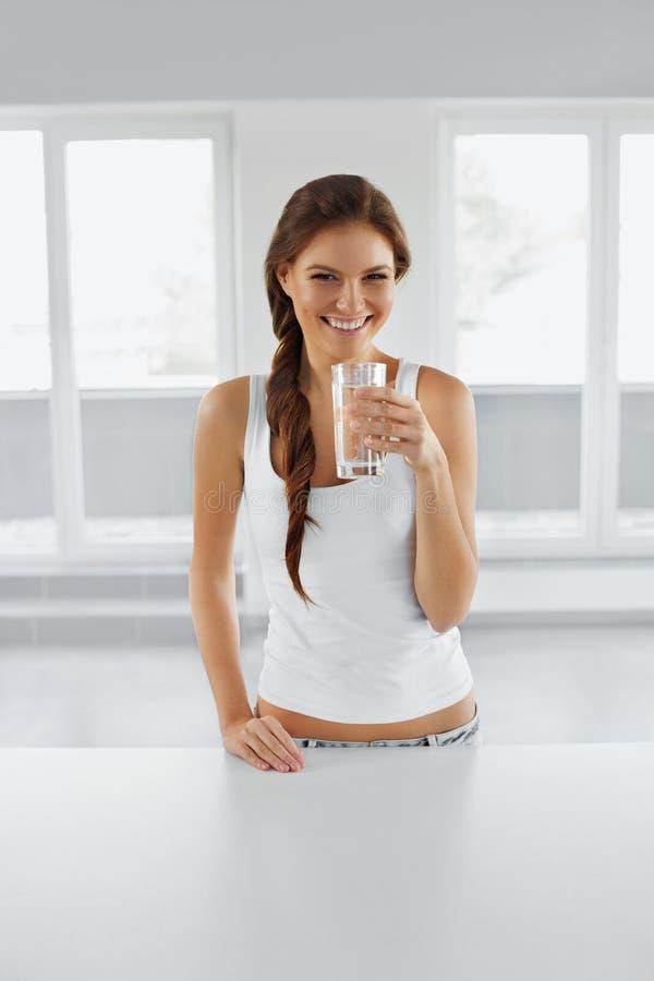 диетпитание принципиальной схемы Счастливая здоровая женщина с стеклом воды пить L стоковое изображение