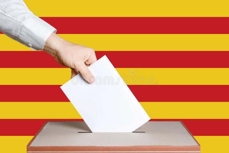 Избиратель держит конверт в руке над голосованием голосования Флаг Каталонии на предпосылке Концепция демократии стоковое фото rf