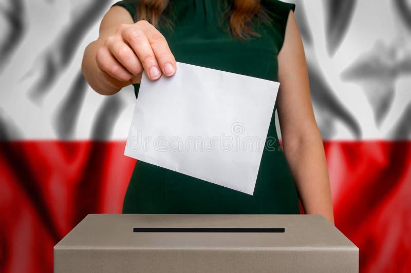 Избрание в Польше - голосующ на урне для избирательных бюллетеней стоковое фото
