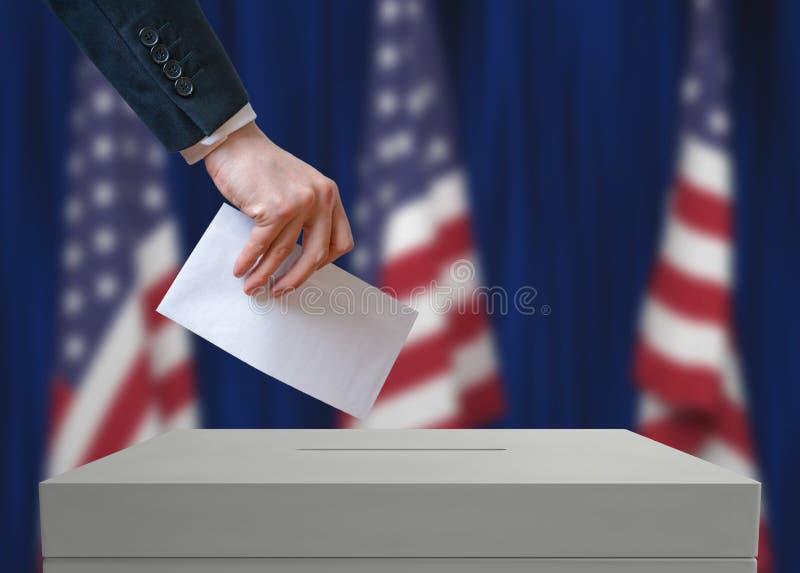Избрание в Соединенных Штатах Америки Избиратель держит конверт в руке над голосованием голосования стоковые фотографии rf