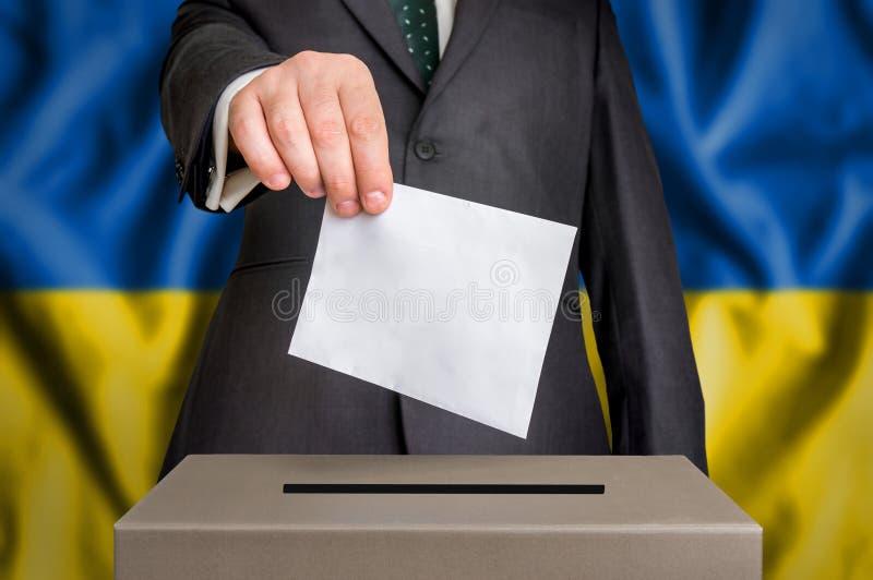 Избрание в Украине - голосующ на урне для избирательных бюллетеней стоковые фото