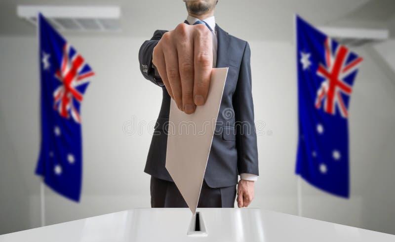 Избрание или референдум в Австралии Избиратель держит конверт в голосовании руки вышеуказанном Флаги австралийца в предпосылке стоковые фото