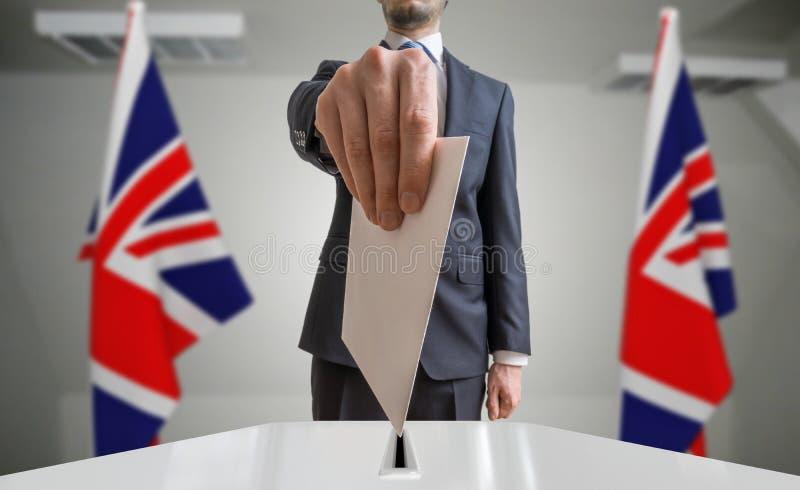 Избрание или референдум в Великобритании Избиратель держит конверт в голосовании руки вышеуказанном Флаги Великобритании в предпо стоковая фотография