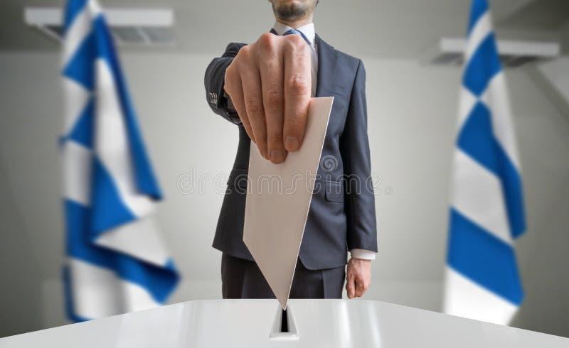 Избрание или референдум в Греции Избиратель держит конверт в голосовании руки вышеуказанном Флаги грека в предпосылке стоковая фотография
