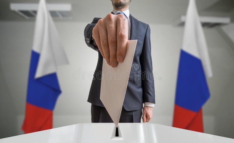 Избрание или референдум в России Избиратель держит конверт в голосовании руки вышеуказанном Флаги русского в предпосылке стоковое изображение rf