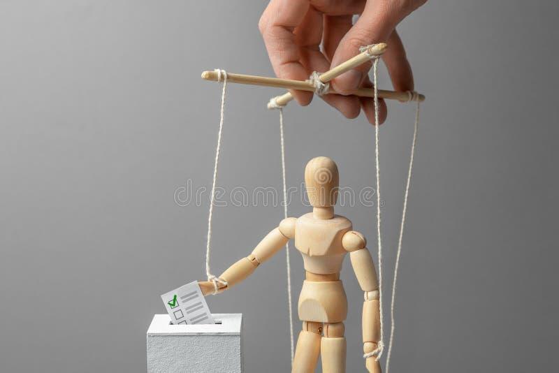 Избрания и голосование человека кладут избирательный бюллетень в коробку Манипуляция и коррупция в голосовании, puppeteer контрол стоковое изображение