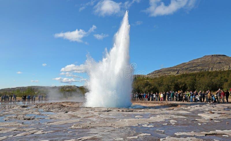 Извержение Strokkur гейзера Исландии на красивый солнечный летний день, с непознаваемыми туристами стоковые изображения rf