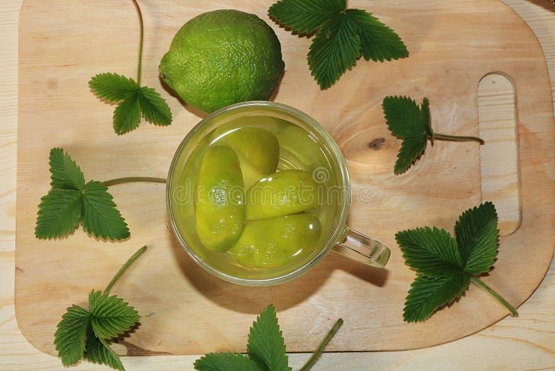Известка в стеклянных кубках и плоде с мятой на деревянном столе стоковое фото