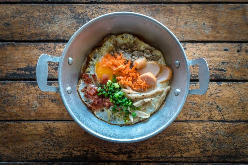 Известной яйца завтрака приготовленные Тайской кухней яичница покрывая с сосиской, овощем и беконом в горячем лотке на деревянном стоковое изображение