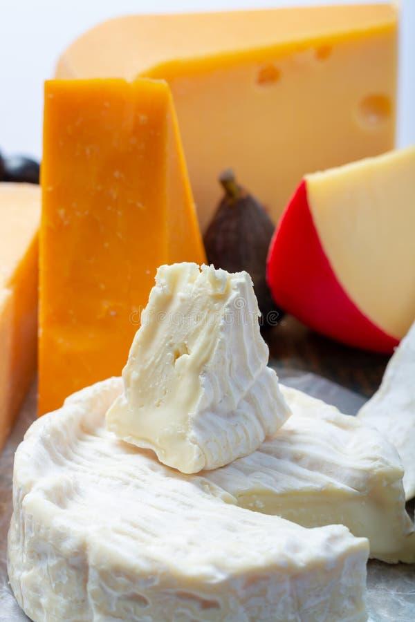 Известные европейские сыры в ассортименте, голландском красном Эдамере шарика и старых сырах с отверстиями, испанским сыром Manch стоковые изображения