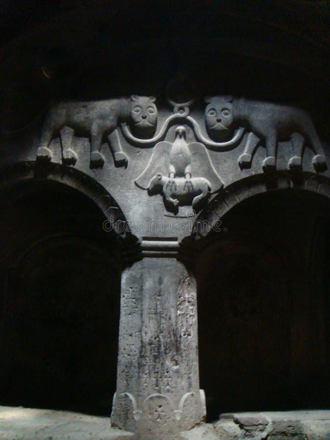 Известные graven 2 кота в камне над 2 дугами, который вытерпел столбец в старом монастыре Geghard в Армении стоковое изображение