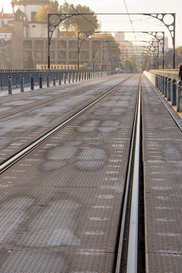 Известный португальский мост с железнодорожными путями в перспективе Мост метро в свете утра в Порту, Португалии стоковые фото