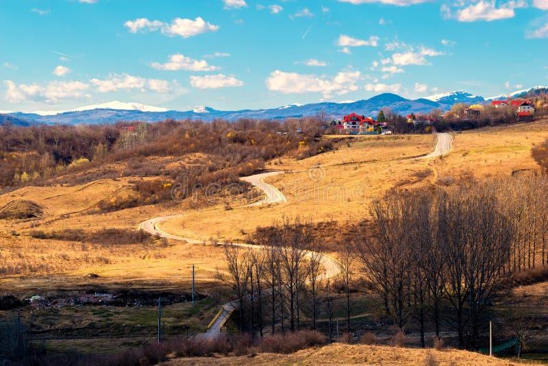 Извилистая дорога через холмы в предыдущем времени и снеге весны покрыла горные пики в далекой предпосылке стоковое изображение