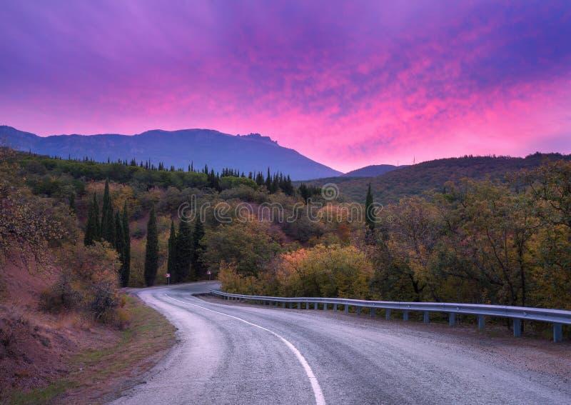 Извилистая дорога горы пропуская через лес с драматическим красочным небом и красными облаками на сумраке в лете стоковое изображение