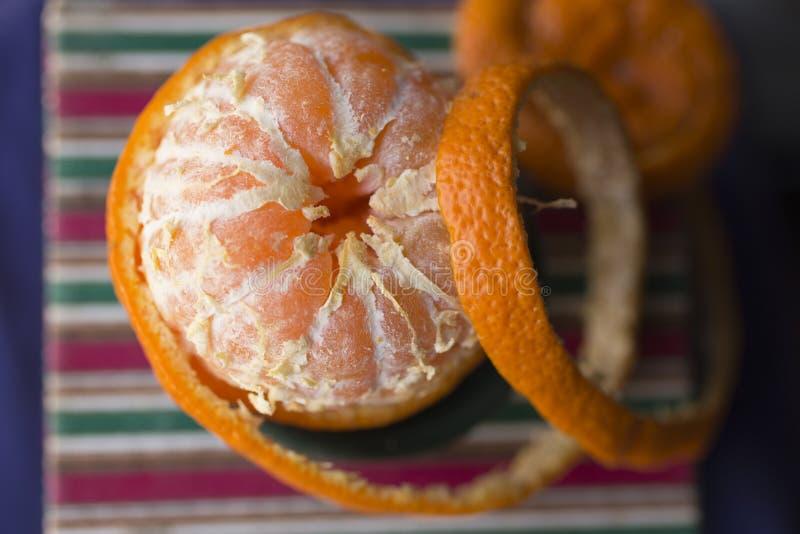 Извлеките корку tangerine Обнажая цитрус стоковые фото
