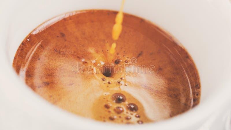 Извлечение эспрессо с богатым crema в чашке стоковое фото