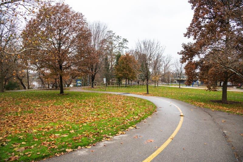 Изгибать путь в парке и облачном небе берега реки стоковое изображение
