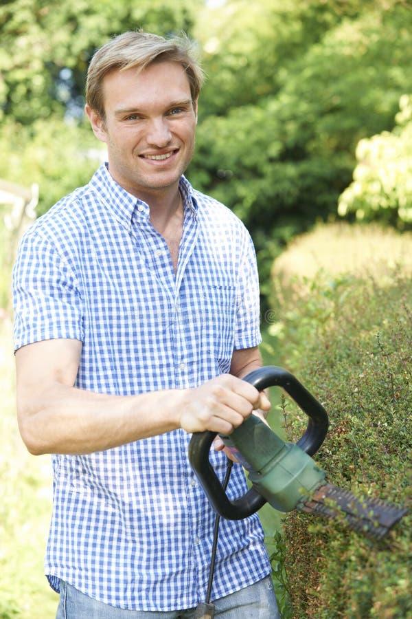 Изгородь сада вырезывания человека с электрическим триммером стоковая фотография rf