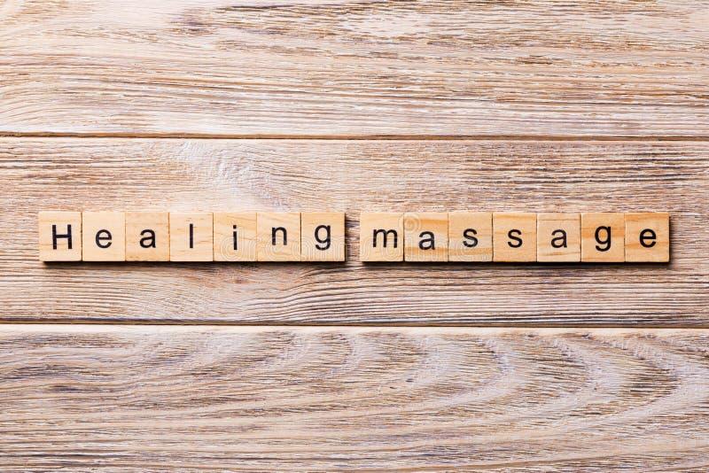 Излечивать слово массажа написанное на деревянном блоке излечивать текст массажа на деревянном столе для ваш desing, концепции стоковое фото rf